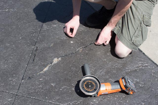 A crack in stamped a stamped concrete driveway that needs to be repaired with Roadware Match Crete Clear.