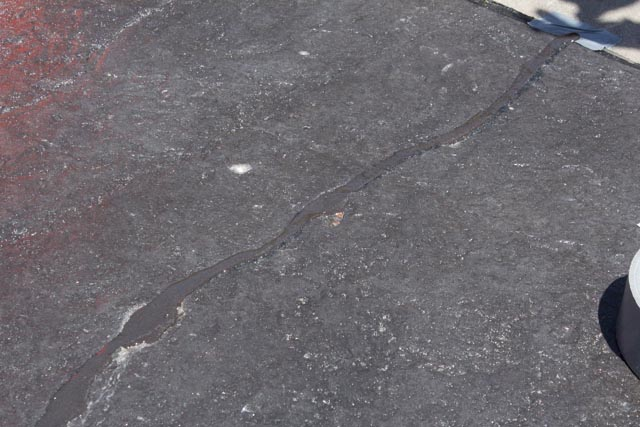 A crack in a stamped concrete driveway repaired with Roadware MatchCrete Clear.