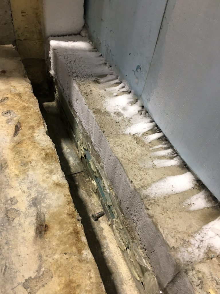 Concrete freezer threshold ready to be repaired with Roadware 10 Minute Concrete Mender.