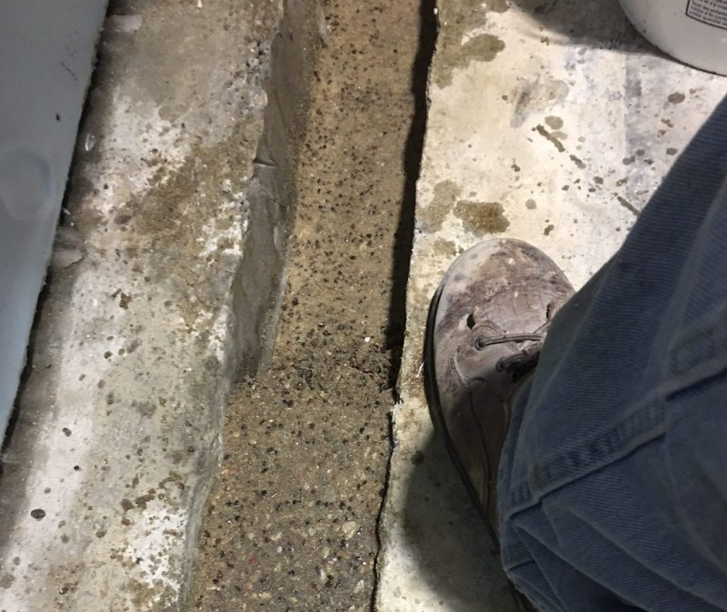 Roadware 10 Minute Concrete Mender and mixed with sand and aggregate is placed in the freezer threshold repair.